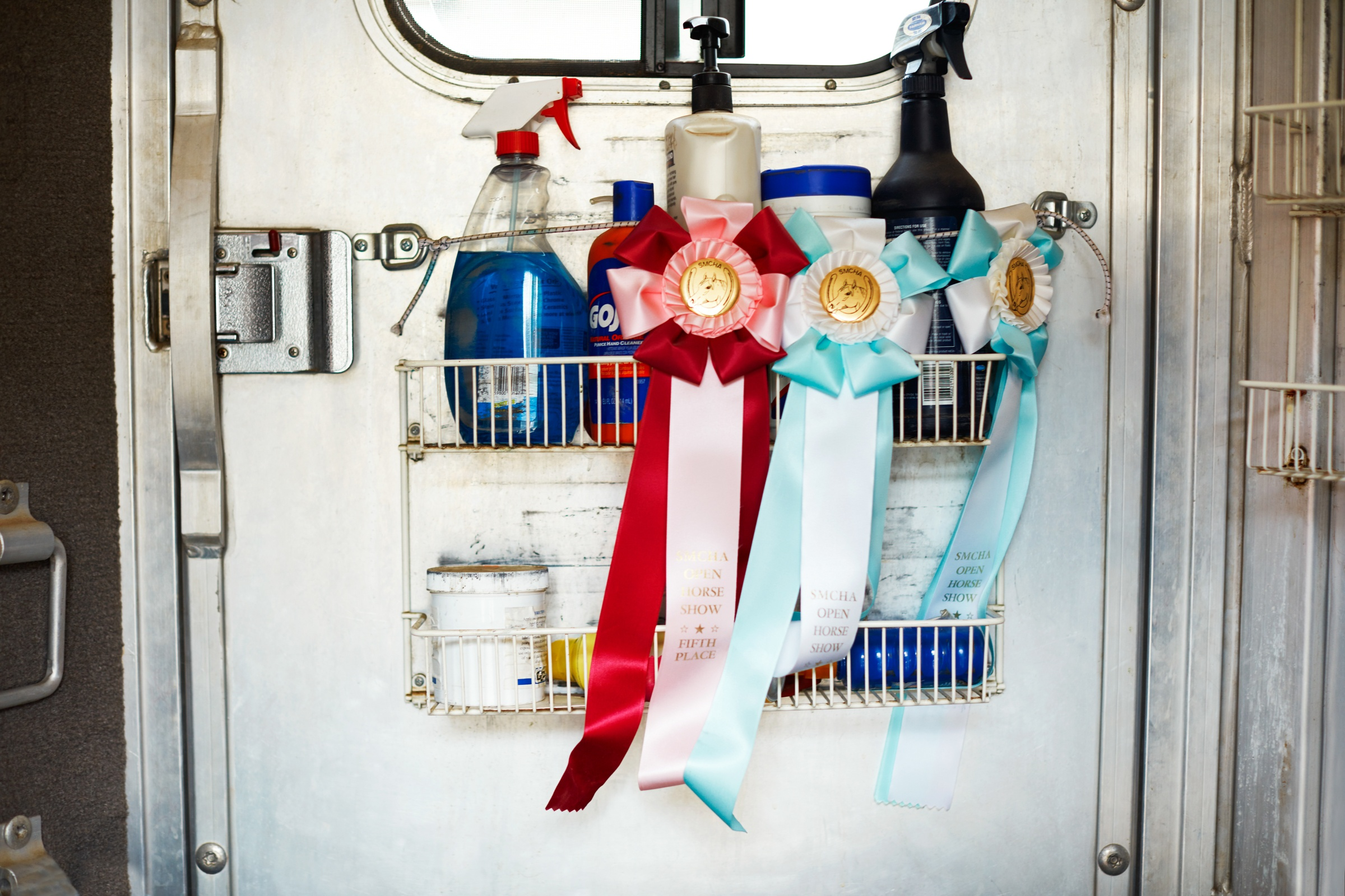 Photo of horse competition ribbons on side of trailer.