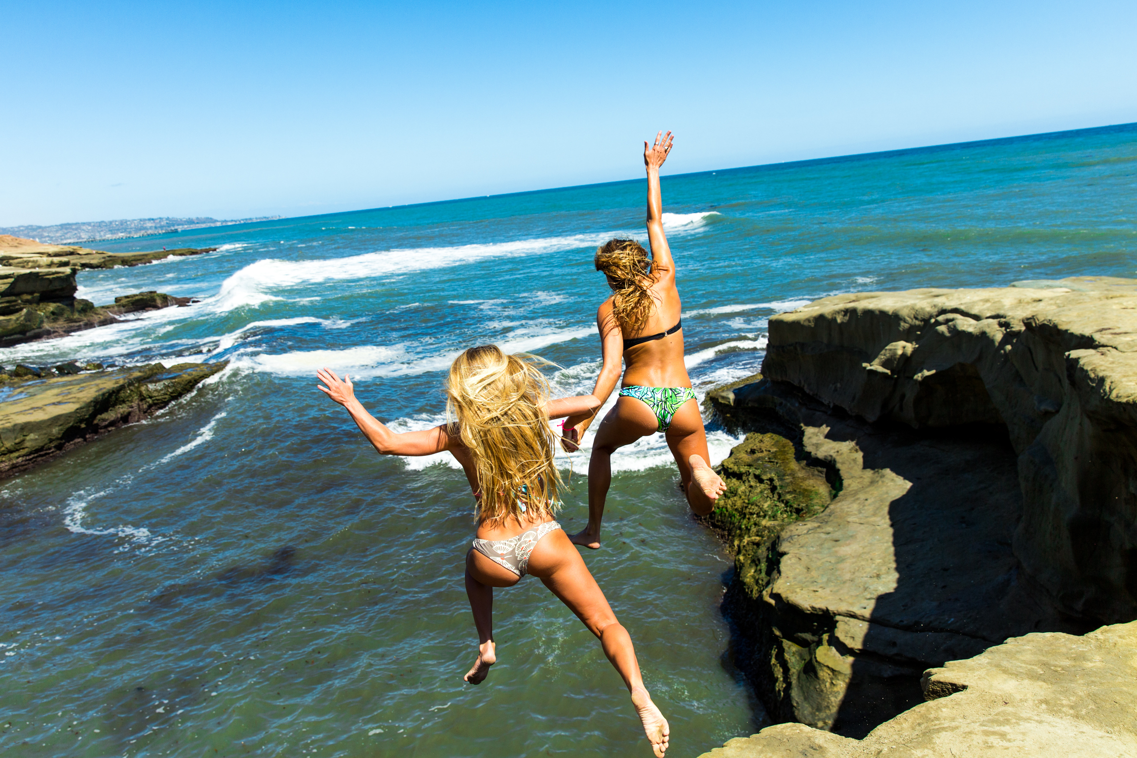 Photo of two women jumping into ocean.