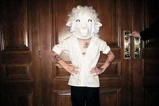 Conceptual photo of man wearing lamb costume.