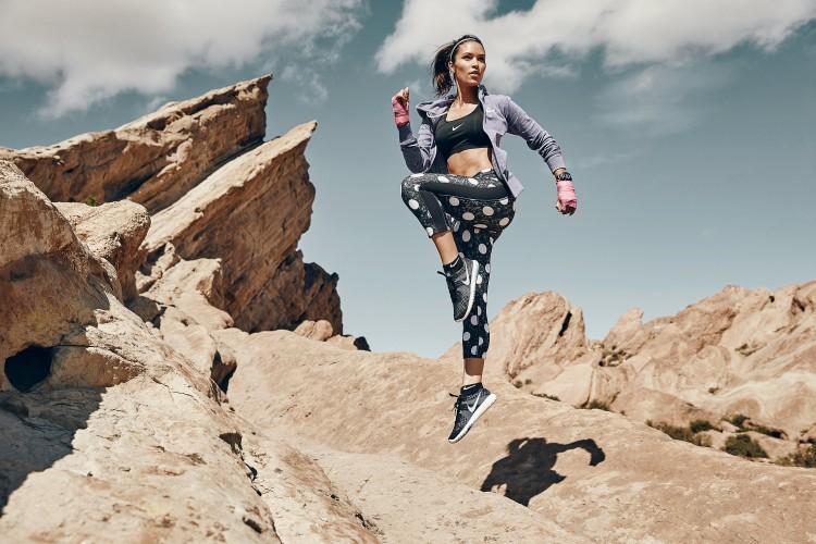 female athlete jumping desert rocks
