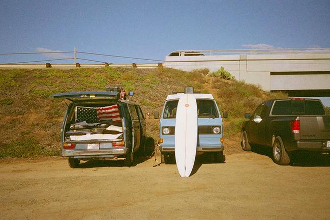 surfboard leaning against van