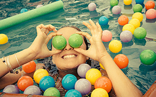 Woman in pool with floaties, rubber balls.