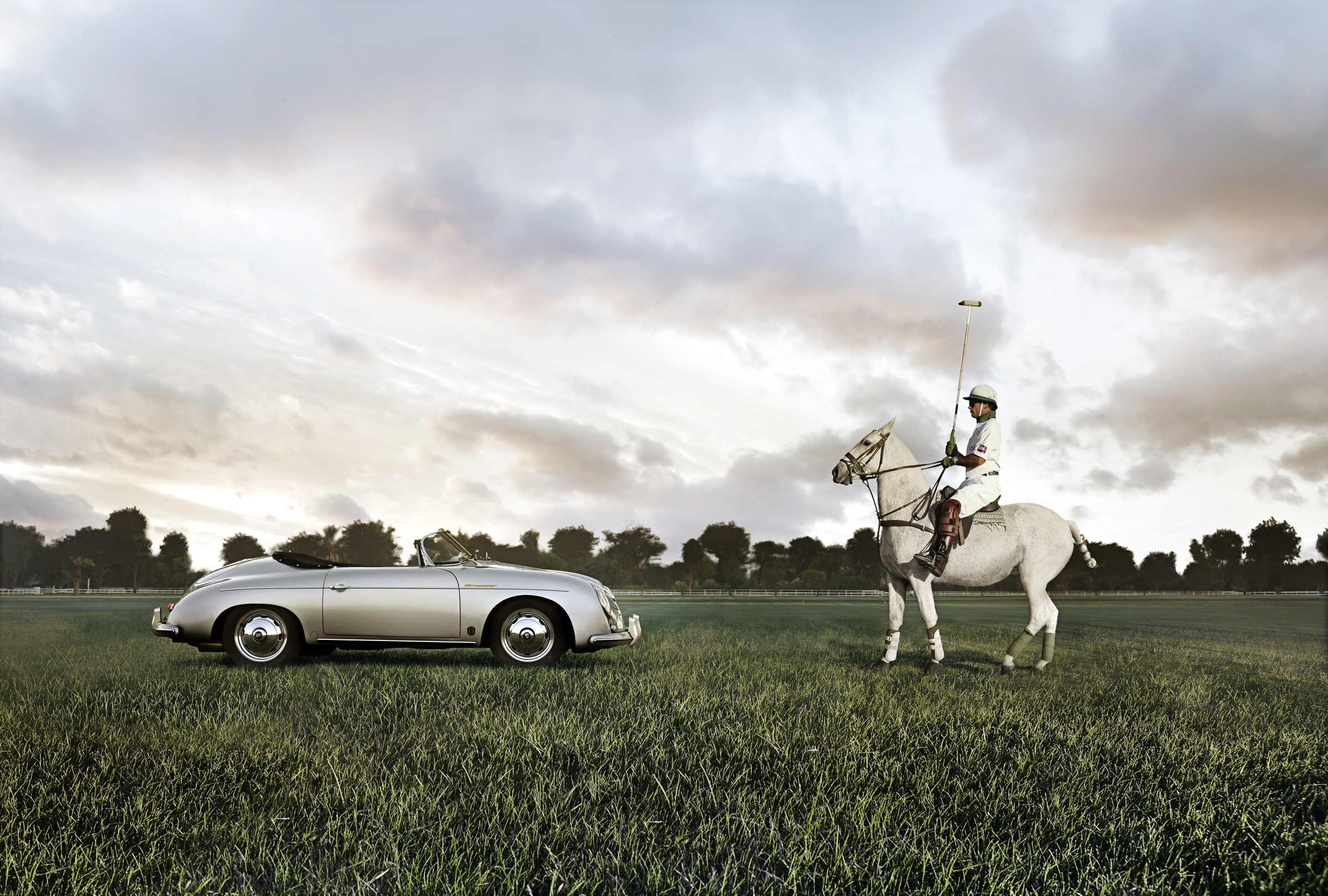 Polo player facing sports car on polo field.