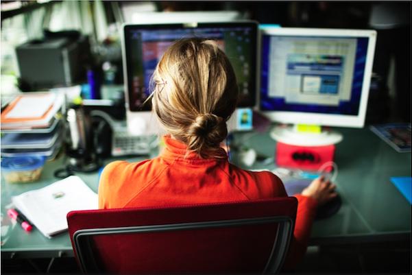 Woman at two computer screens